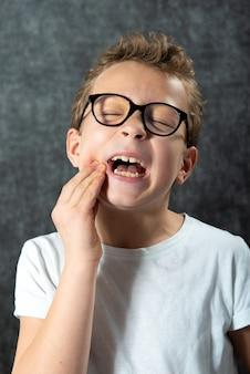 O menino do retrato tem uma dor de dente. expressão