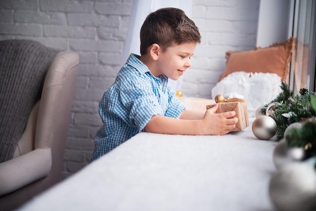 O menino doce na janela está olhando para a caixa de presente. a atmosfera do ano novo ou do natal