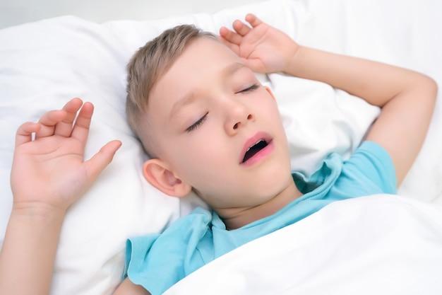 O menino dorme com a boca aberta.