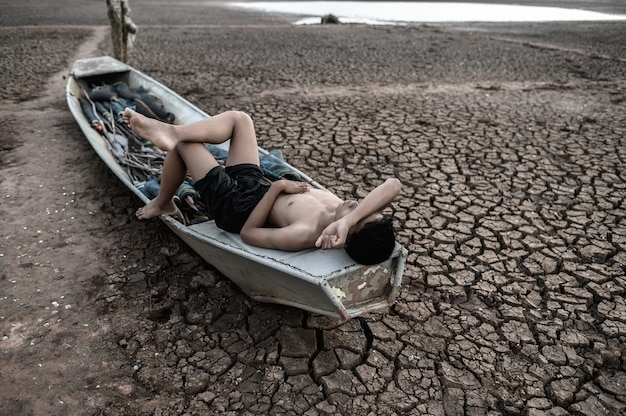O menino dormiu em um barco de pesca e colocou as mãos na testa no chão seco, o aquecimento global