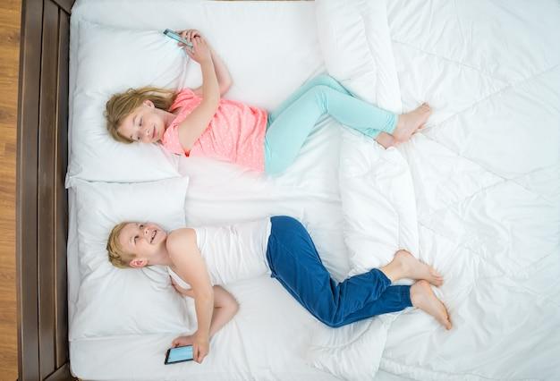 O menino e a menina com telefones deitaram na cama. vista de cima