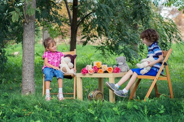 O menino e a menina se sentar em uma mesa na rua entre árvores