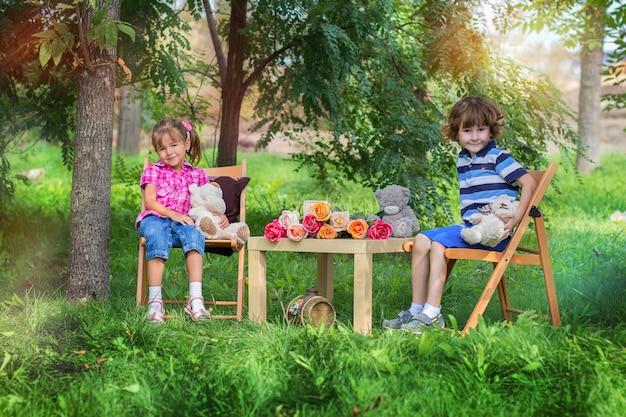 O menino e a menina se sentar em uma pequena mesa na rua entre árvores