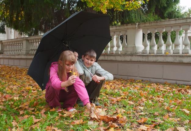 O menino e a menina sentam-se sob um guarda-chuva e recolher folhas caídas