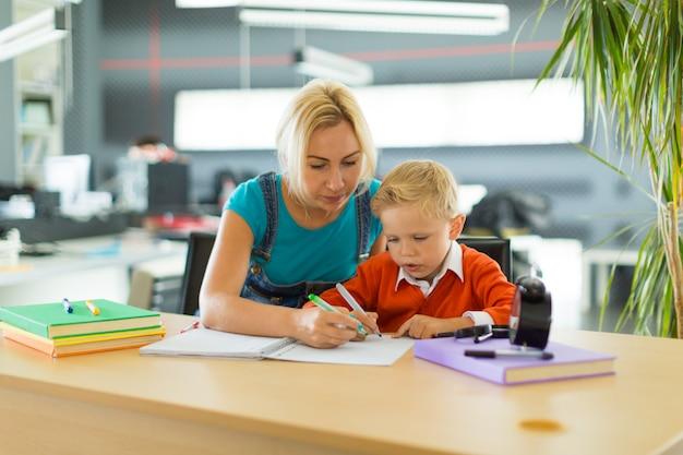 O menino e a mulher bonitos sentam-se na mesa no escritório e tiram