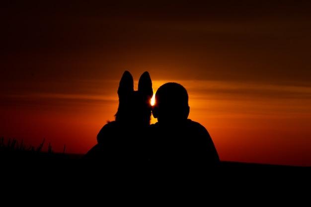 O menino e o cachorro malinois no fundo de um lindo pôr do sol