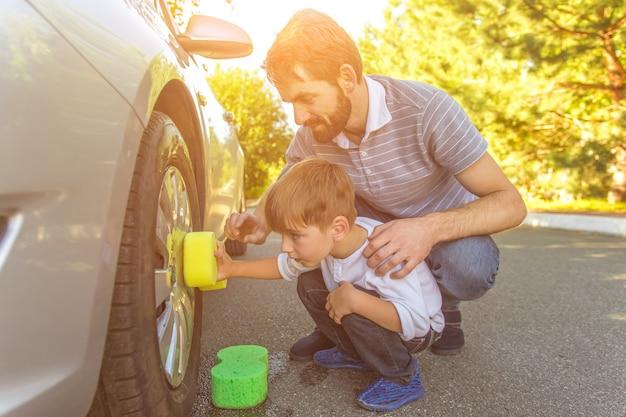 O menino e o pai lavando um carro em um fundo ensolarado