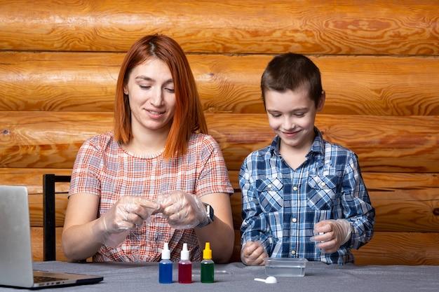 O menino e sua mãe, os cientistas despejam uma mistura de um tubo de ensaio em um recipiente