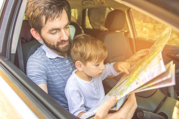 O menino e um pai olham para o mapa dentro do carro