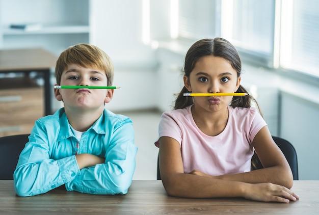 O menino e uma menina brincando com um lápis na mesa