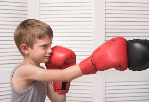 O menino em luvas de boxe luta com a mão de um homem em uma luva.