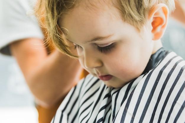 O menino em um salão de cabeleireiro