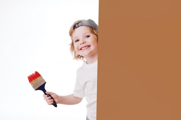 O menino em um t-shirt branco com uma escova de pintura em suas mãos, pinturas na parede, escreve.