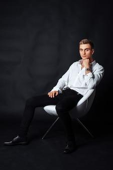 O menino em uma camisa branca, sentado em uma cadeira. o conceito de vida