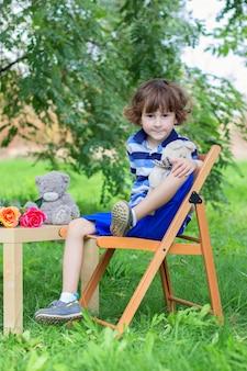 O menino em uma t-shirt azul listrada senta-se em um banquinho ao ar livre entre os verdes