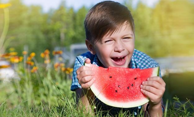 O menino engraçado come melancia ao ar livre no parque de verão