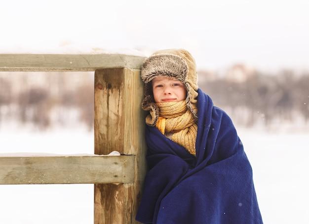 O menino enrolado em um cobertor no inverno na natureza. congelada e triste