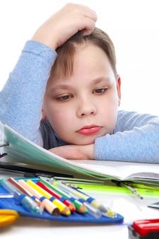 O menino entediado atrás de uma mesa com livros