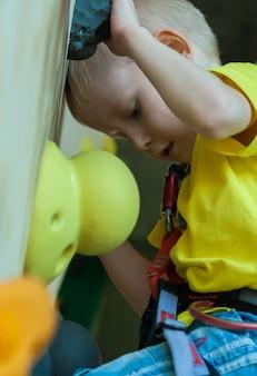 O menino escala a parede da parede de escalada. recreação ativa, esportes infantis.