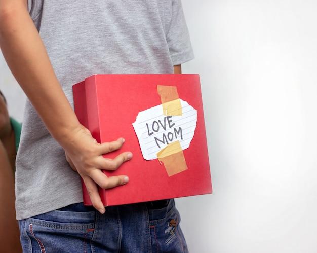 O menino esconde uma caixa de presente para sua mãe nas costas de sua própria.
