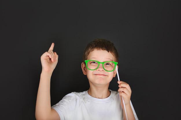 O menino esperto com vidros verdes é pensativo perto do quadro.