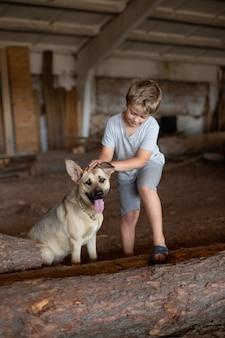 O menino está acariciando seu cachorro