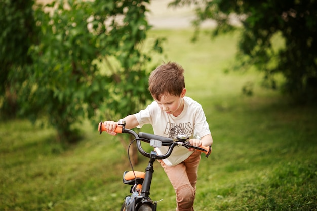 O menino está andando de bicicleta na rua