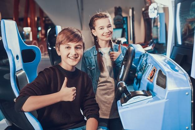 O menino está andando de carro no arcade a irmã está torcendo
