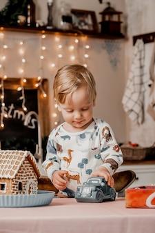 O menino está brincando com um presente de ano novo enquanto está na cozinha decorada com guirlandas e decorações de natal