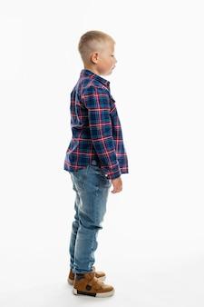 O menino está de pé. um colegial gordo e bonito de jeans, uma camisa e uma camiseta branca. altura toda. espaço em branco. vertical. vista lateral.