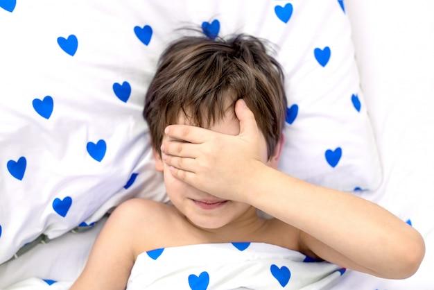 O menino está deitado em uma cama com corações azuis, o rosto nas mãos. emoções sem rosto. cor branca, vista superior