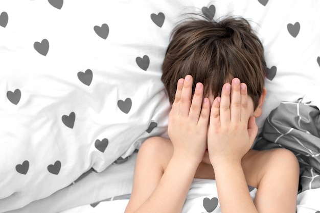 O menino está deitado em uma cama com corações cinzentos, o rosto nas mãos. emoções sem rosto. cor branca, vista superior