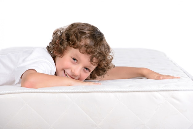 O menino está deitado no colchão e sorrindo.
