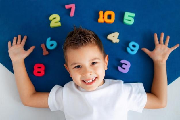 O menino está deitado no tapete azul em torno dele números de 1 a 10