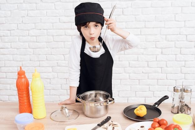 O menino está dominando a profissão de cozinheiro