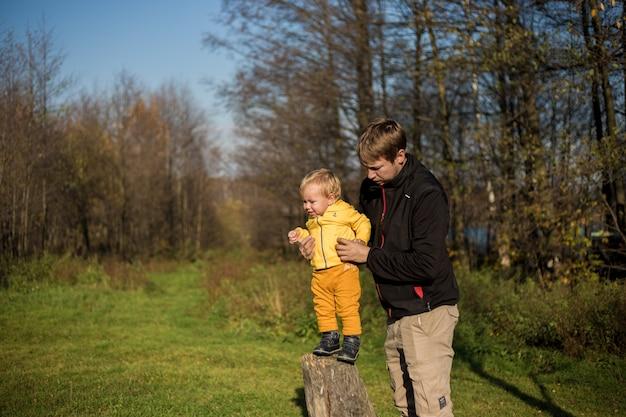 O menino está em um toco de árvore, o pai o apóia no contexto da floresta.
