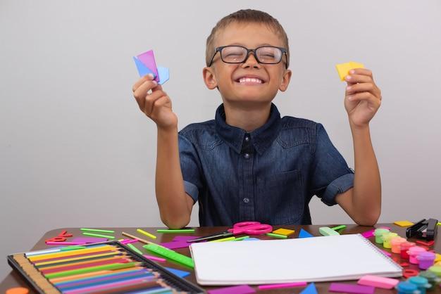 O menino está empenhado em criatividade na mesa desenha.