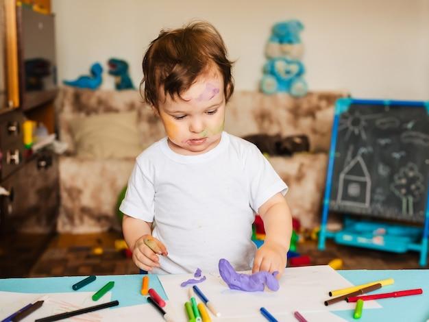 O menino está empenhado em modelar de massa para modelar figuras.
