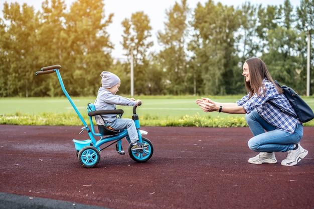 O menino está indo com sucesso para a mãe em um triciclo infantil