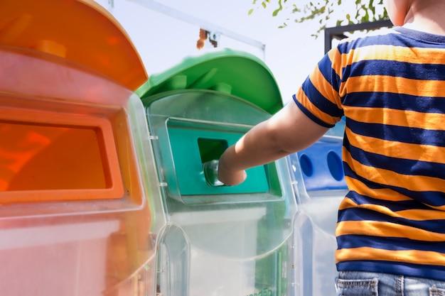 O menino está levando o lixo para o lixo no parque. ele colocou resíduos de garrafas no lixo.