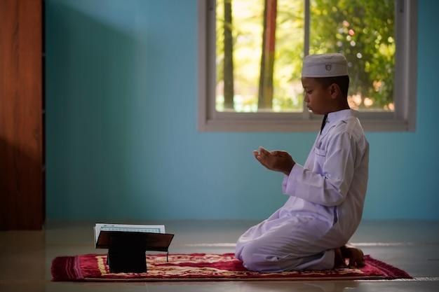 O menino está orando e aprendendo a recitar o alcorão na mesquita, um conceito da próxima geração do islã.