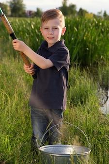 O menino está pescando no campo
