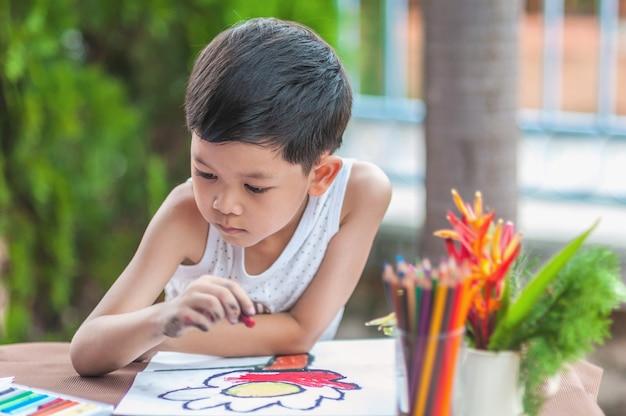 O menino está pintando a imagem colorida em casa.