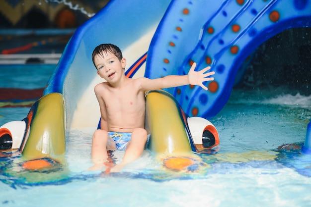 O menino está rolando com um toboágua em um parque aquático em little rock