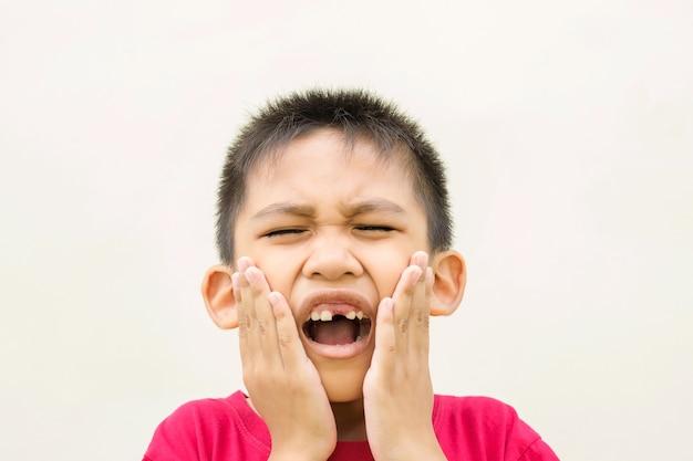 O menino está segurando a mão na bochecha e no rosto vermelho de dor de dente.