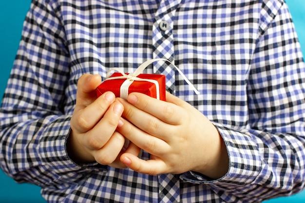 O menino está segurando um presente vermelho nas mãos dando parabéns pelo feriado de aniversário prese ...