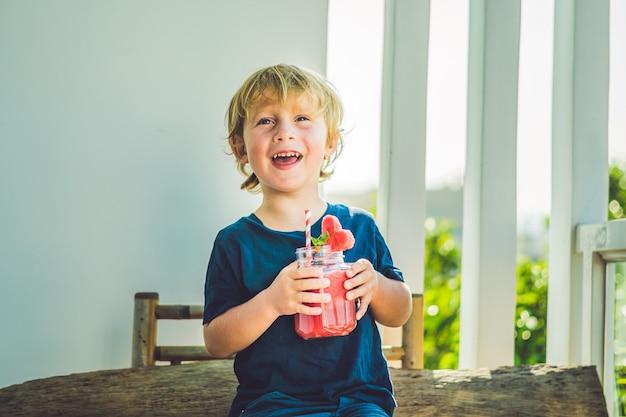 O menino está segurando um smoothie de melancia saudável em um frasco de vidro com hortelã e canudo listrado