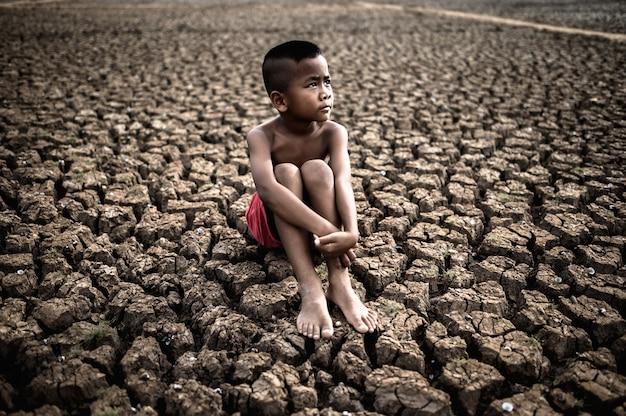 O menino está sentado, abraçando os joelhos dobrados e olhando para o céu para pedir chuva em solo seco.