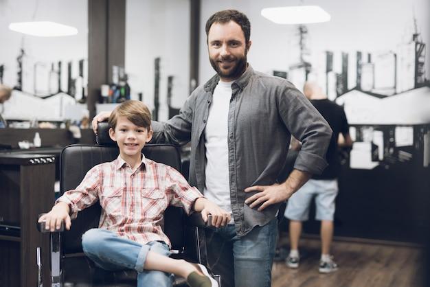 O menino está sentado na barbearia do cabeleireiro