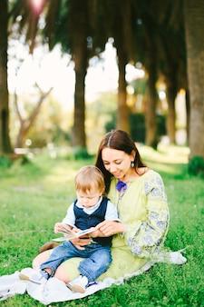 O menino está sentado no colo da mãe lendo um livro em um piquenique no parque